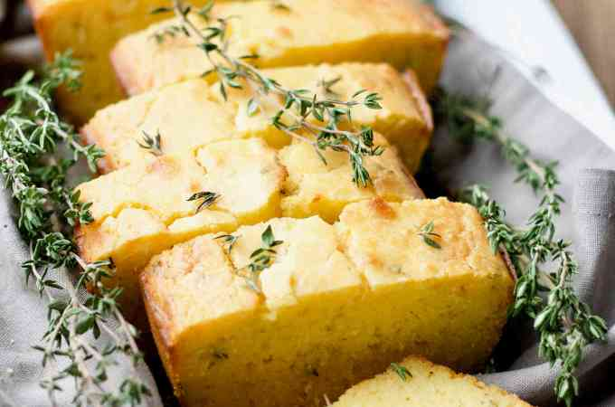 A loaf of kefir fermented honey thyme sourdough cornbread sliced and placed in a serving dish.