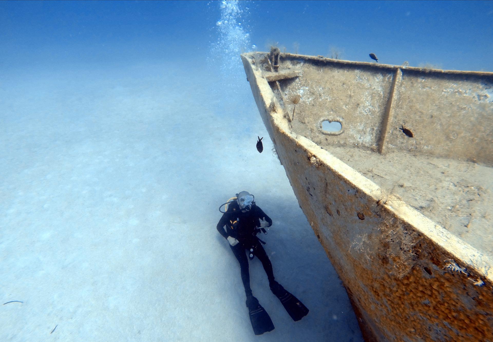 Plongeur avec épave de bateau dans l'océan