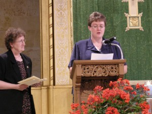 Sister Penny Bingham, prioress looks on as Sister Peggy Venteicher professes to live the Benedictine vows of stability, obedience, and fidelity to the monastic way of life.