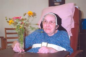 Sister Leonarda appreciating the beauty of flowers