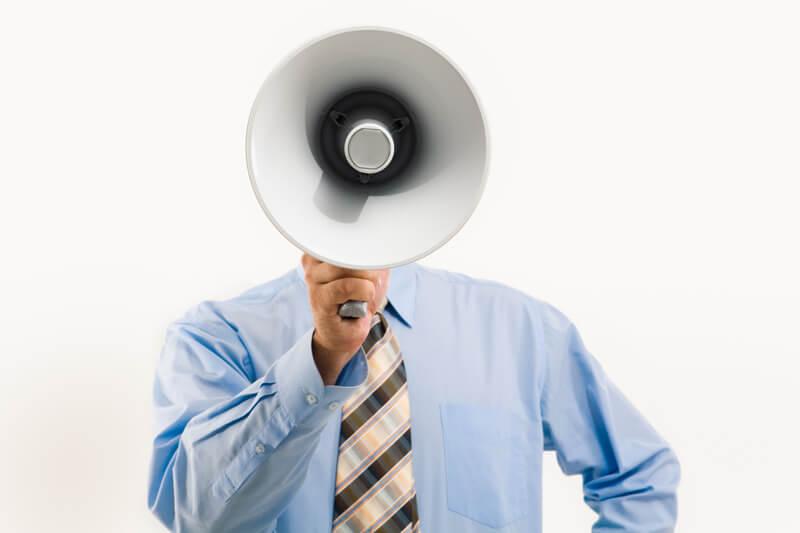 Un homme en costume tiens un haut parleur devant son visage