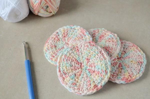 Tunisian crochet face scrubbies in a pile next to a crochet hook