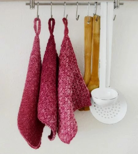 Three beautiful crochet washcloths on hooks, next to a strainer, a ladle and two bamboo spatulas