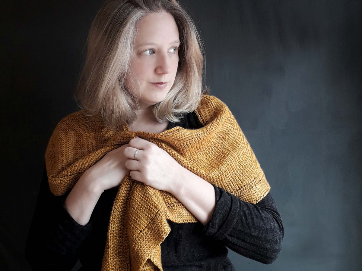 a woman dressed in black holds a solid, golden shawl around her shoulders. She's looking to her left and is standing in front of a dark background.