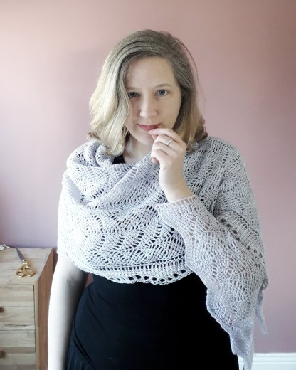 a white woman wears a grey lace shawl across her shoulders. Her hand is raised to her lips as she looks directly at the camera. She is dressed in black and stands in front of a light pink wall