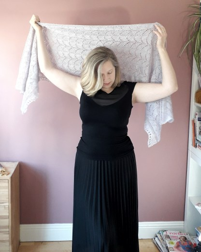 a white woman holds a grey lace shawl over her head. She is dressed in black and stands in front of a light pink wall