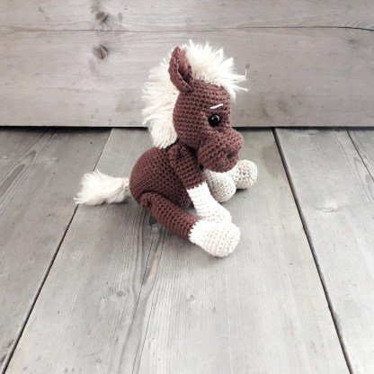 side view of a brown crochet horse soft toy sitting on a table top with its front hooves resting on its back legs