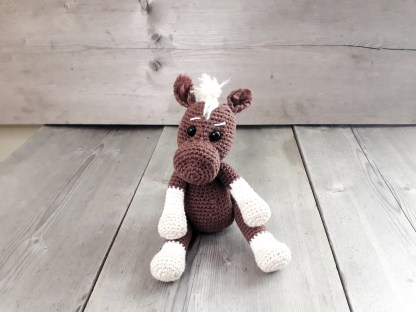 a brown crochet horse soft toy sits on a table top with its front hooves resting on its back legs