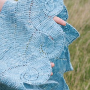 close up of a light blue shawl worked in spirals of tunisian crochet