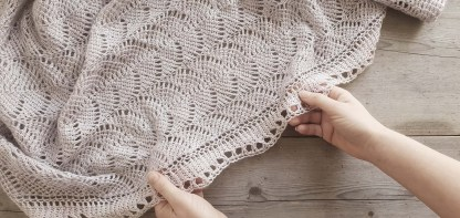 a close up of a grey lace shawl lying on an old and weathered wooden table top. Two hands hold the shawl gently.