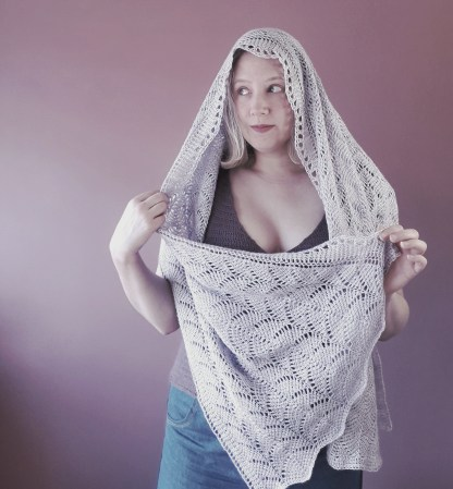 a 3/4 length portrait of a woman drape din a grey, lace shawl. She is wearing blue jeans and a dark purple top and stands in front of a pink wall