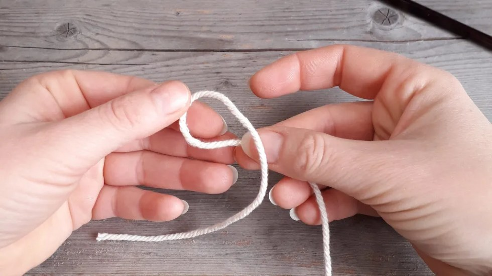 two hands holding up a strand of white yarn. The strands are crossed, with the tail on top.