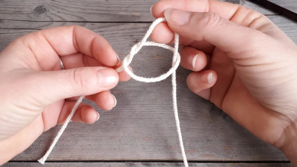 The yarn that was pinched between index and middle finger has been drawn through the crossed strands to make a loop.
