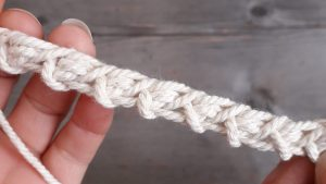 a stretchy chain made of white yarn held over a scrubbed wooden tabletop