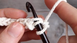 stretchy chain made from white yarn held over a wooden table. Hook has been inserted into the next chain