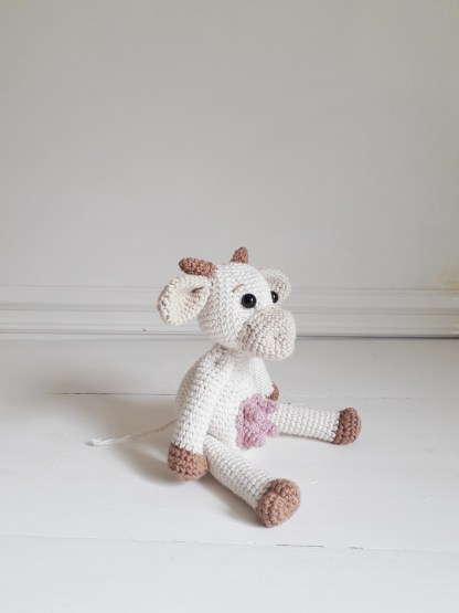 a white, crochet cow sits on a white table with her legs in front of her and her body turned to the right.