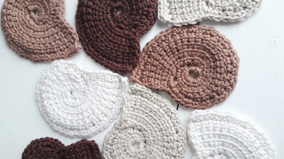 a selection of spiral-shaped crochet scrubbies arranged on a white, wooden tabletop