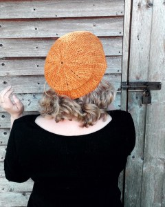 a woman is standing with her back to the camera, wearing a warm yellow, tunisian crochet slouchy hat