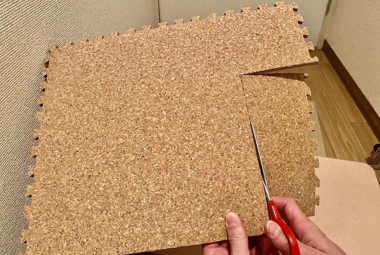 コルクマットの敷き方の画像12。洗面所の床の形に合わせて、コルクマットを切っています。