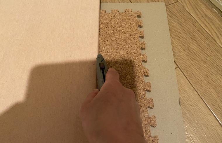 コルクマットの敷き方の画像6。コルクマットをカッターで切っています。