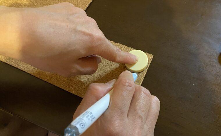 コルクシートを使ったマグネットの作り方画像1。コルクシートにマグネットを置いて大きさを型取りしています。