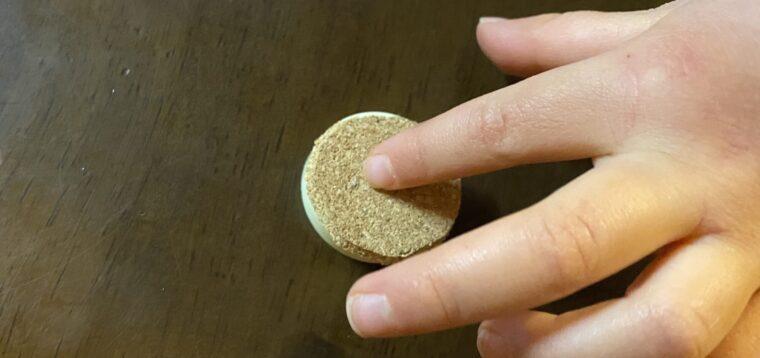 コルクシートを使ったマグネットの作り方画像4。マグネットの上部に形どったコルクシートを子供が付けています。