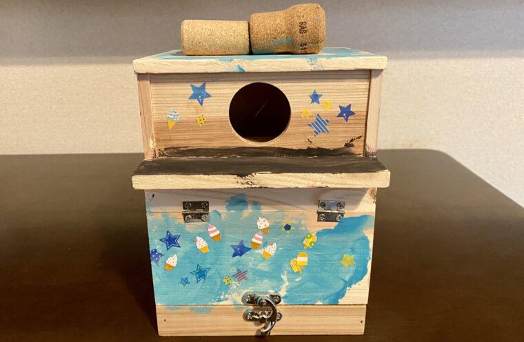 野鳥の巣箱の前側部分に、星とアイスクリームのステッカーを貼った画像。