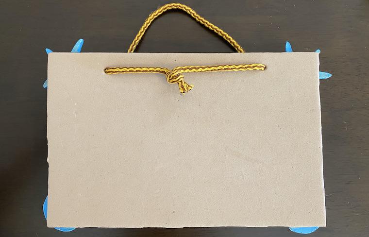 コルクボードに通したヒモの長さを調節して結んだ画像