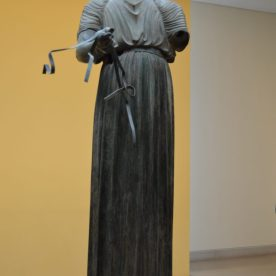Bronze statue of a charioteer on display at the Delphi Archaeological Museum in Delphi, Greece