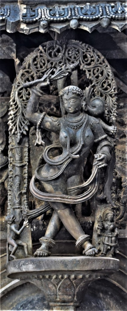 Madanike chasing a monkey - A bracket figure mounted on the exterior wall of the Belur Chennakeshava Temple in Karnataka, India