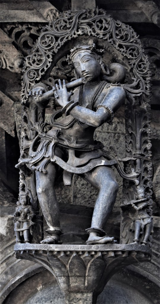 Sculpture of a flute playing male musician mounted on a pillar on the south side of Chennakeshava Temple in Belur, Karnataka, India