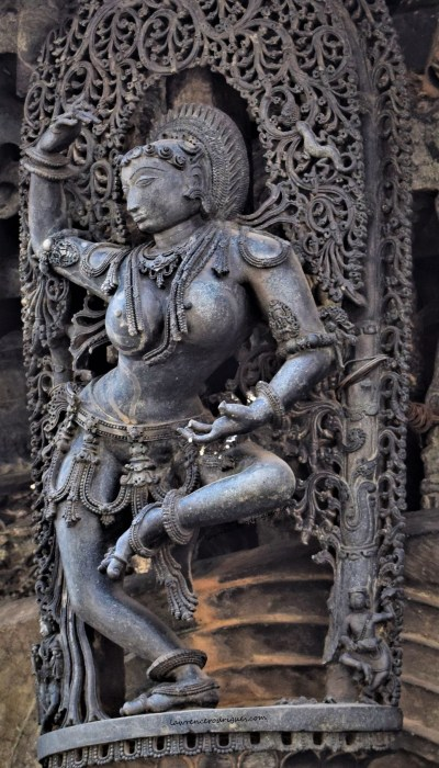 Belur Chennakeshava Temple - Sculpture of a dancing shilabalike with a lizard chasing a fly in the background mounted on a pillar at the north entrance
