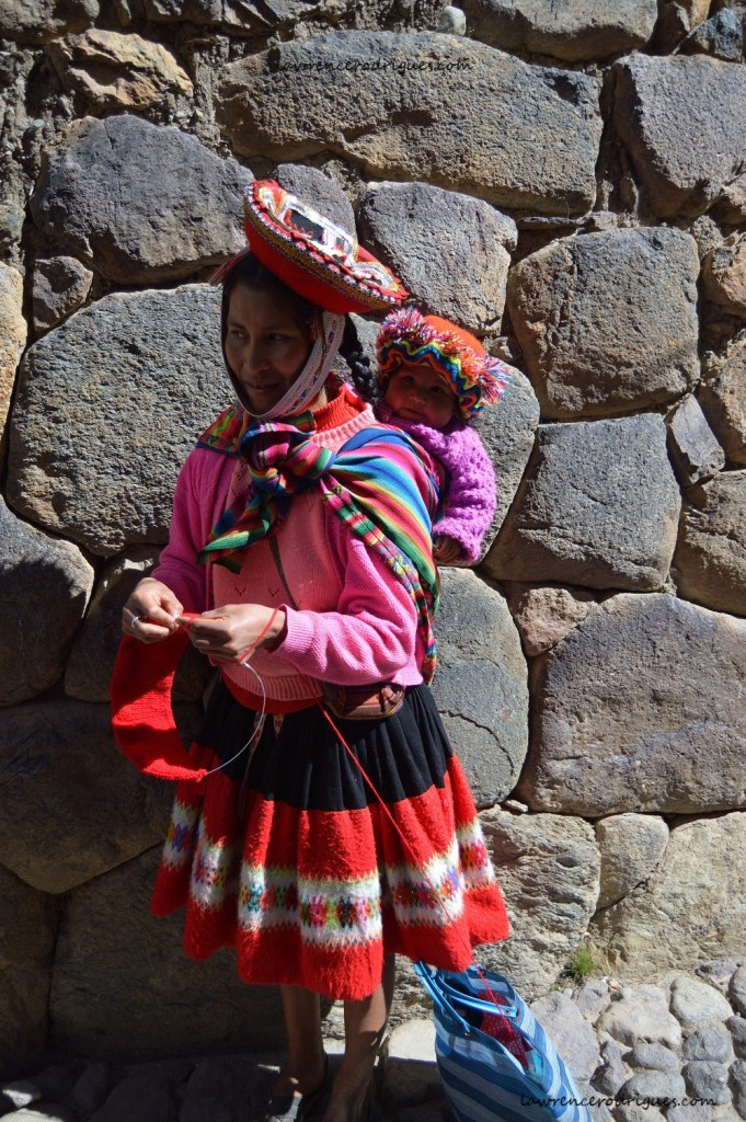 An indigenous woman carrying a child in an Inca village near Ollantaytambo in the Cuzco region of Peru