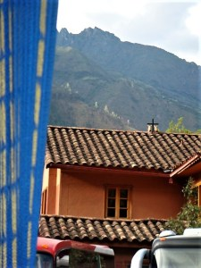 A house with a cross and two bulls on the rooftop at Ollantaytambo
