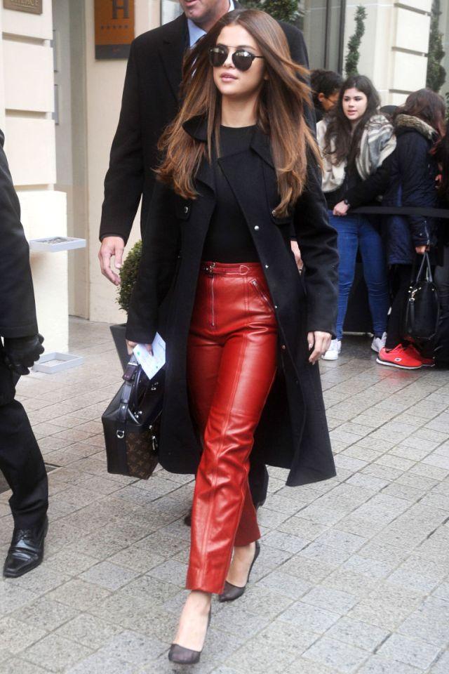 Брюки из красной кожи, которые удачно сочетает с темным топом и черным пальто.