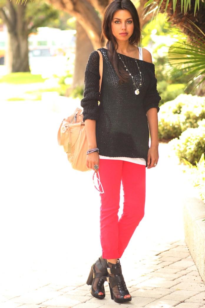 Красные брюки с черной блузкой и светлой сумкой.