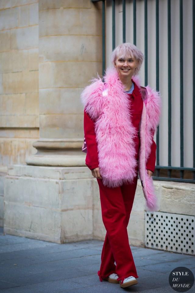 Красные брюки с меховой безрукавкой ярко розового цвета.