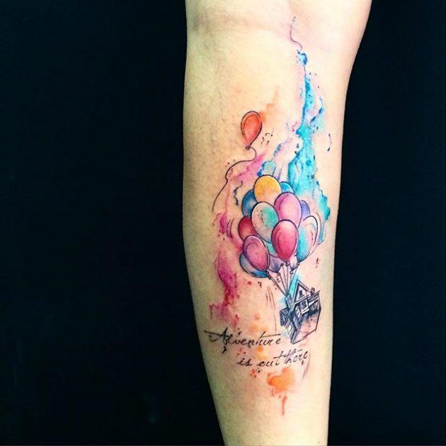На фото: акварельная татуировка в виде дома летящего на воздушных шарах.