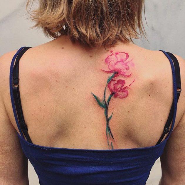 На фото: акварельная татуировка - цветок на спине.