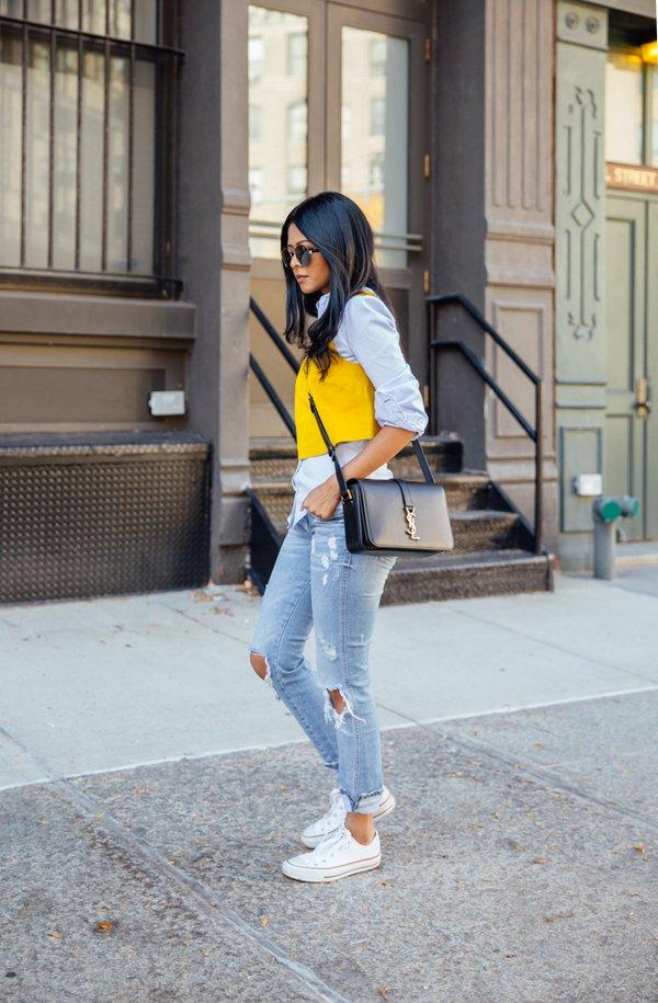 На фото: белые кеды Converse в сочетании с рваными джинсами и блузой.