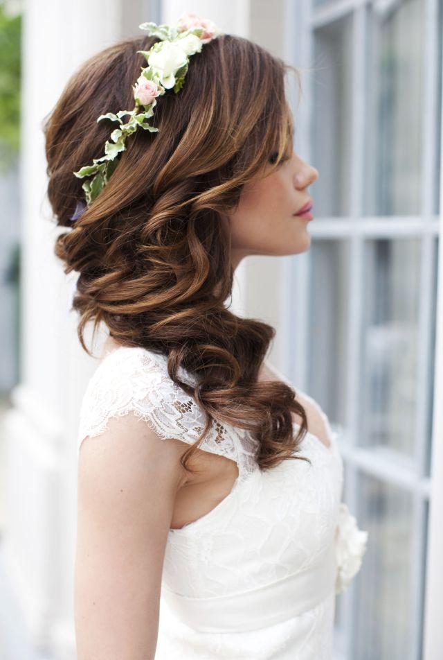 На фото: свадебная прическа с крупными локонами и украшением в виде ободка из цветов.