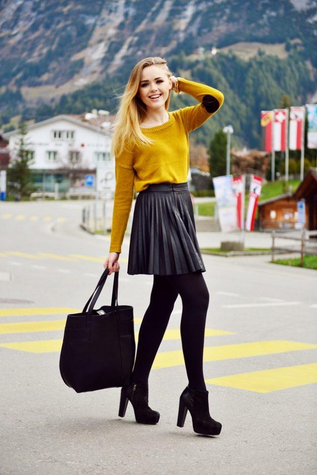 На фото: короткая раслешенная черная кожаная юбка яркое сочетание с кофтой оранжевого цвета.