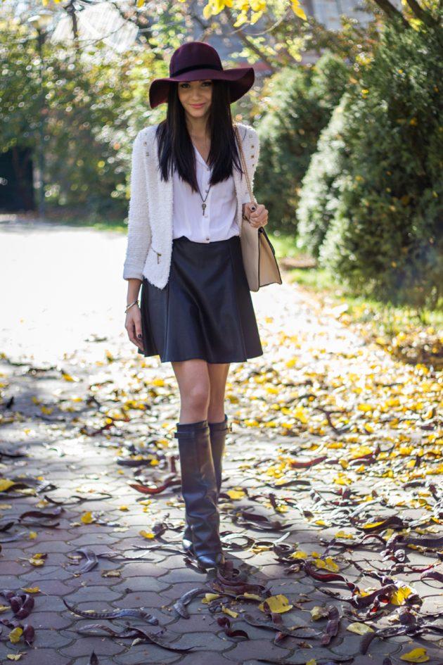 На фото: короткая раслешенная черная кожаная юбка с завышенной талией яркое сочетание с белой блузкой и белым кардиганом.