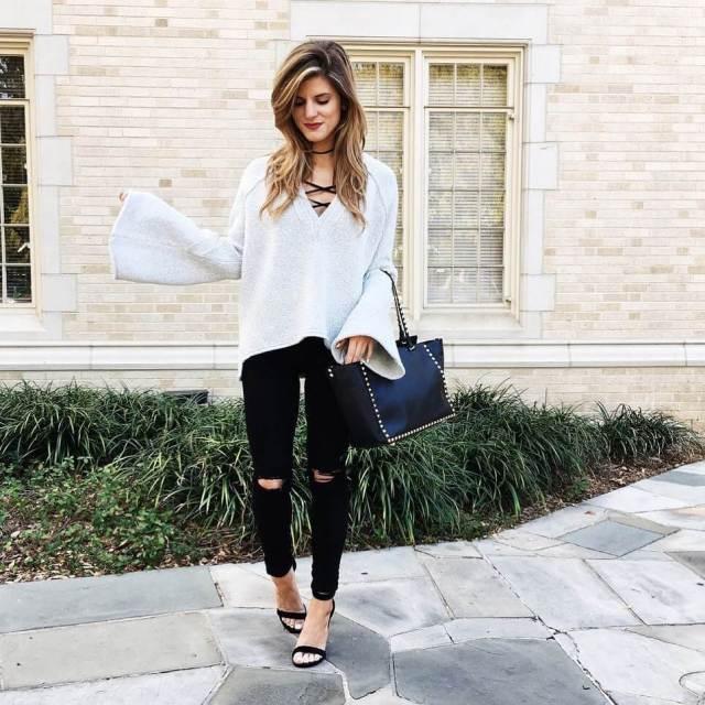 На фото: Casual стиль -  белый свитер оверсайз с черными рваными джинсами и босоножками.