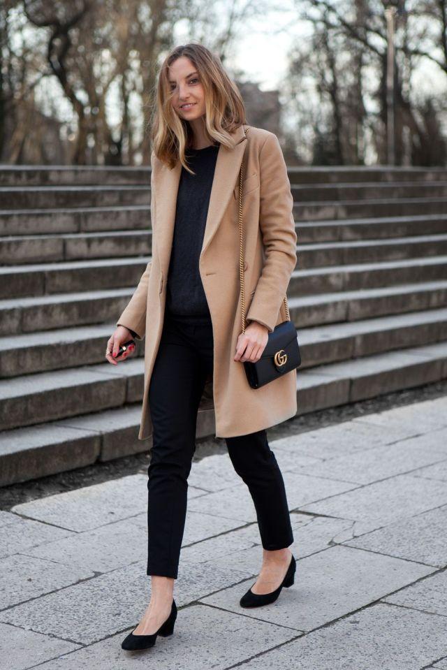 На фото: светло коричневое пальто: новое красивое сочетание с черными прямыми брюками, черной кофтой и черными туфлями.