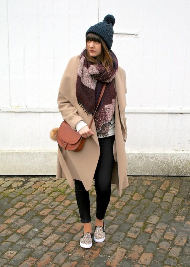Бежевое пальто в сочетании с черными узкими джинсами - модные вещи декабря.