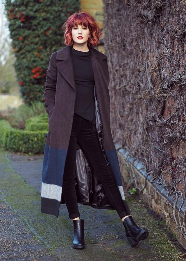Модные вещи декабря - многоцветное длинное пальто в сочетании с черными джинсами.