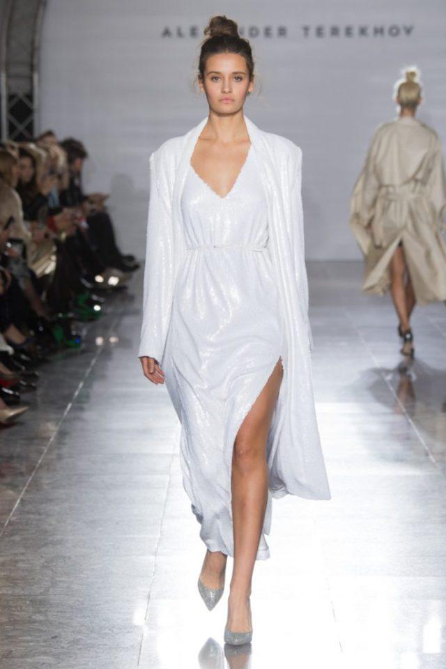 Белого цвета платье с глубоким разрезом и плащ с блестящим отливом из коллекции Александра Терехова весна-лето 2017.