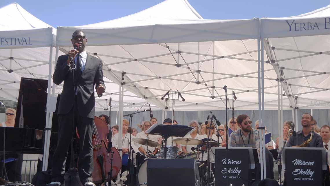 Photo of Marcus Shelby speaking in front of his orchestra