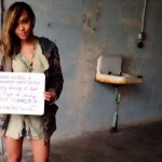 Photo of Jackie Ramos holding a hand-written sign at the Unseen Project at Alcatraz